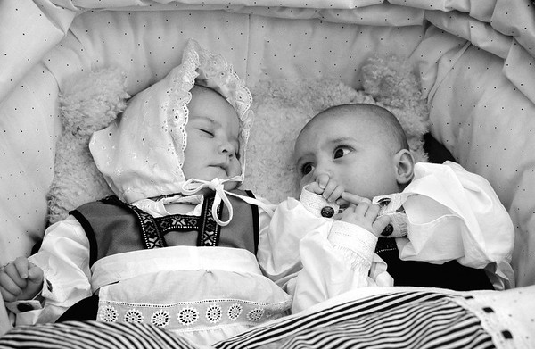 Babies dressed for the occasion during the 17th of May national day. A noteworthy aspect of the Norwegian Constitution Day is its very non-military nature. All over Norway, children's parades with an abundance of flags form the central elements of the celebration. Each elementary school district arranges its own parade with marching bands between schools. The parade takes the children through the community, often making stops at homes of senior citizens, war memorials, etc. The longest parade is in Oslo, where some 100,000 people travel to the city centre to participate in the main festivities.  Oslo, Norway, 2000.