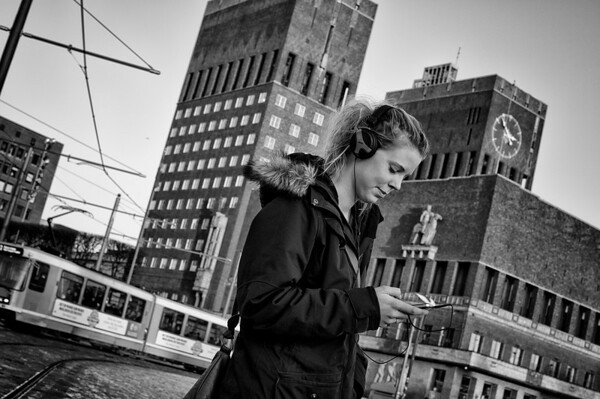 """Young woman in front of the city hall. Oslo City Hall (Norwegian: Oslo rådhus) houses the city council, city administration, and art studios and galleries. The construction started in 1931, but was paused by the outbreak of World War II, before the official inauguration in 1950. Its characteristic architecture, artworks and the Nobel Peace Prize ceremony, held on 10 December, makes it one of Oslo's most famous buildings. It was designed by Arnstein Arneberg and Magnus Poulsson. The roof of the eastern tower has a 49-bell carillon which plays every hour. It is situated in Pipervika in central downtown Oslo. The area was completely renovated and rebuilt to make room for the new city hall, back in the late 1920s. In June 2005 it was named Oslo's """"Structure of the Century"""", with 30.4% of the votes.  Oslo, Norway, 2012."""