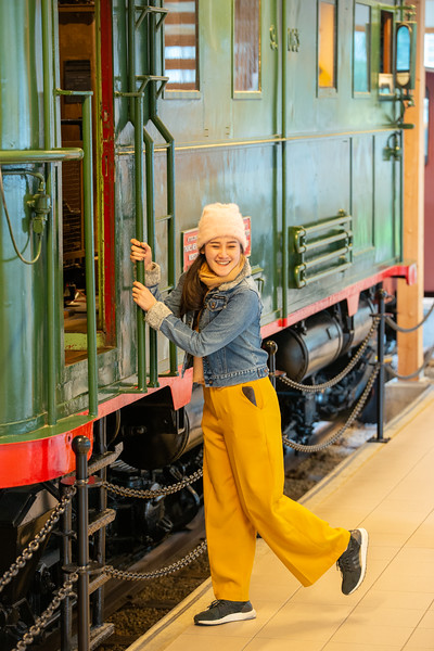 A tourist posing at the old train at Flam Museum. Flåm Line between Flåm and Myrdal, is one of the steepest railway tracks in the world. A former rail station building in Flåm now houses a museum dedicated to the Flåm railway. The village of Flåm has been a tourist destination and currently receives almost 450,000 visitors a year with many riding the 20-kilometre (12 mi) Flåm Line.<br /> <br /> Flåm is a village in Flåmsdalen, at the inner end of the Aurlandsfjorden, Aurland, in Sogn og Fjordane county, Norway.