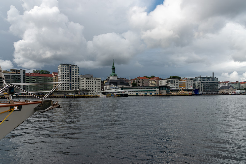 Waterfront, near Bergenhus Fortress at Bergen, Norway. Bergen, historically called Bjørgvin, is a city as well as municipality in Hordaland on the west coast of Norway. Bergen is the second-largest city in Norway. The city centre and northern neighbourhoods are on Byfjorden, 'the city fjord', and the city is surrounded by mountains; Bergen is known as the 'city of seven mountains'.<br /> <br /> Bergen Port is Norway's busiest in terms of both freight and passengers with over 300 cruise ship calls a year bringing nearly a half a million passengers to Bergen.