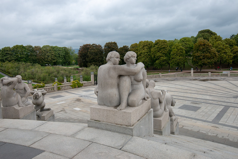 """The Vigeland installation, Oslo, Norway is located in the present centre of Frogner Park. The sculpture area in Frogner Park covers 80 acres and features 212 bronze and granite sculptures, all designed by Gustav Vigeland.<br /> <br /> At the highest point in Frogner Park lies the park's most popular attraction, the Monolith (Monolitten). The Monolith towers 14.12 metres (46.32 ft) high and is composed of 121 human figures rising towards the sky. The Monolith Plateau is a platform in the north of Frogner Park made of steps that houses the Monolith totem itself. 36 figure groups reside on the elevation, representing a """"circle of life"""" theme. Access to the Plateau is via eight wrought iron gates depicting human figures. The gates were designed between 1933 and 1937 and erected shortly after Vigeland died in 1943. At the end of the installation's axis there is a sundial. Most of the statues in the park are made of Iddefjord granite."""