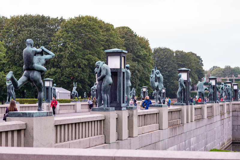 Vigeland installation in Frogner Park, Oslo, Norway. The sculpture area in Frogner Park covers 80 acres (320,000 m2) and features 212 bronze and granite sculptures, all designed by Gustav Vigeland. The Bridge was the first part to be opened to the public, in 1940. The Bridge forms a 100 metre (328 ft)-long, 15 metre (49 ft)-wide connection between the Main Gate and the Fountain, lined with 58 sculptures, including one of the park's more popular statues, Angry Boy (Sinnataggen). Visitors could enjoy the sculptures while most of the park was still under construction. At the end of the bridge lies the Children's Playground, a collection of eight bronze statues showing children at play.<br /> <br /> Most of the statues in the park are made of Iddefjord granite.