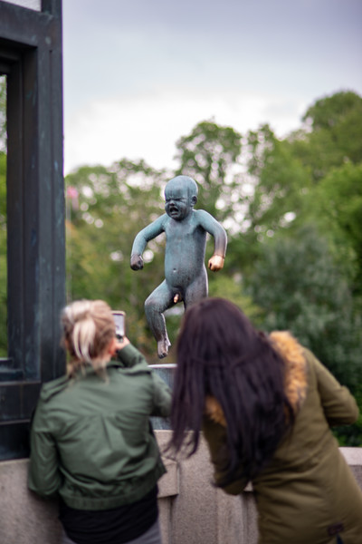 """Visitors take pictures of """"Angry Boy"""" (Sinnataggen). Vigeland installation in Frogner Park, Oslo, Norway. The sculpture area in Frogner Park covers 80 acres (320,000 m2) and features 212 bronze and granite sculptures, all designed by Gustav Vigeland. The Bridge was the first part to be opened to the public, in 1940. The Bridge forms a 100 metre (328 ft)-long, 15 metre (49 ft)-wide connection between the Main Gate and the Fountain, lined with 58 sculptures, including one of the park's more popular statues, Angry Boy (Sinnataggen). Visitors could enjoy the sculptures while most of the park was still under construction. At the end of the bridge lies the Children's Playground, a collection of eight bronze statues showing children at play.<br /> <br /> Most of the statues in the park are made of Iddefjord granite."""