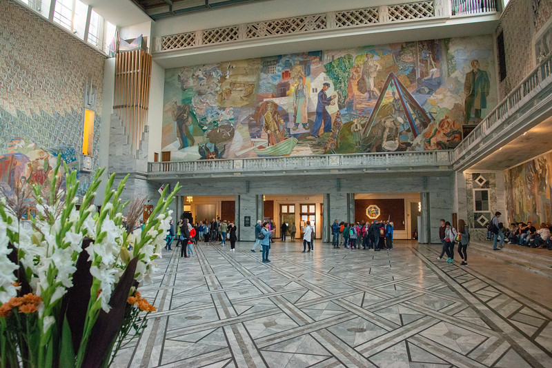 Henrik Sørensen's decoration in the Oslo City Hall. Oil painting 1938-1950. Inside Oslo City Hall, Rådhusplassen, Oslo, Norway. The building's main hall was decorated by Henrik Sørensen and Alf Rolfsen. The Hall is 31 metres wide, 39 metres long and around 21 metres high. The floor and parts of the walls are clad in marble. The room has a series of wall paintings depicting Norway and Oslo between the wars and also during occupation. They also depict the growth of commercial activity in the city, including the rise of the labour movement. Various monarchs and the city's patron saint, St. Hallvard are also depicited.