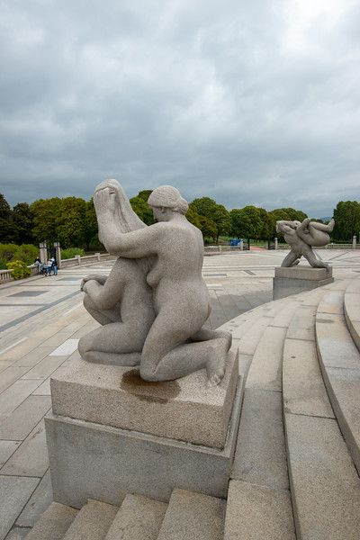"The Vigeland installation, Oslo, Norway is located in the present centre of Frogner Park. The sculpture area in Frogner Park covers 80 acres and features 212 bronze and granite sculptures, all designed by Gustav Vigeland.<br /> <br /> At the highest point in Frogner Park lies the park's most popular attraction, the Monolith (Monolitten). The Monolith towers 14.12 metres (46.32 ft) high and is composed of 121 human figures rising towards the sky. The Monolith Plateau is a platform in the north of Frogner Park made of steps that houses the Monolith totem itself. 36 figure groups reside on the elevation, representing a ""circle of life"" theme. Access to the Plateau is via eight wrought iron gates depicting human figures. The gates were designed between 1933 and 1937 and erected shortly after Vigeland died in 1943. At the end of the installation's axis there is a sundial. Most of the statues in the park are made of Iddefjord granite."