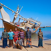 Oman, Al Ashkharah - Bengali maintanance crew posing in front of 'their' dhow