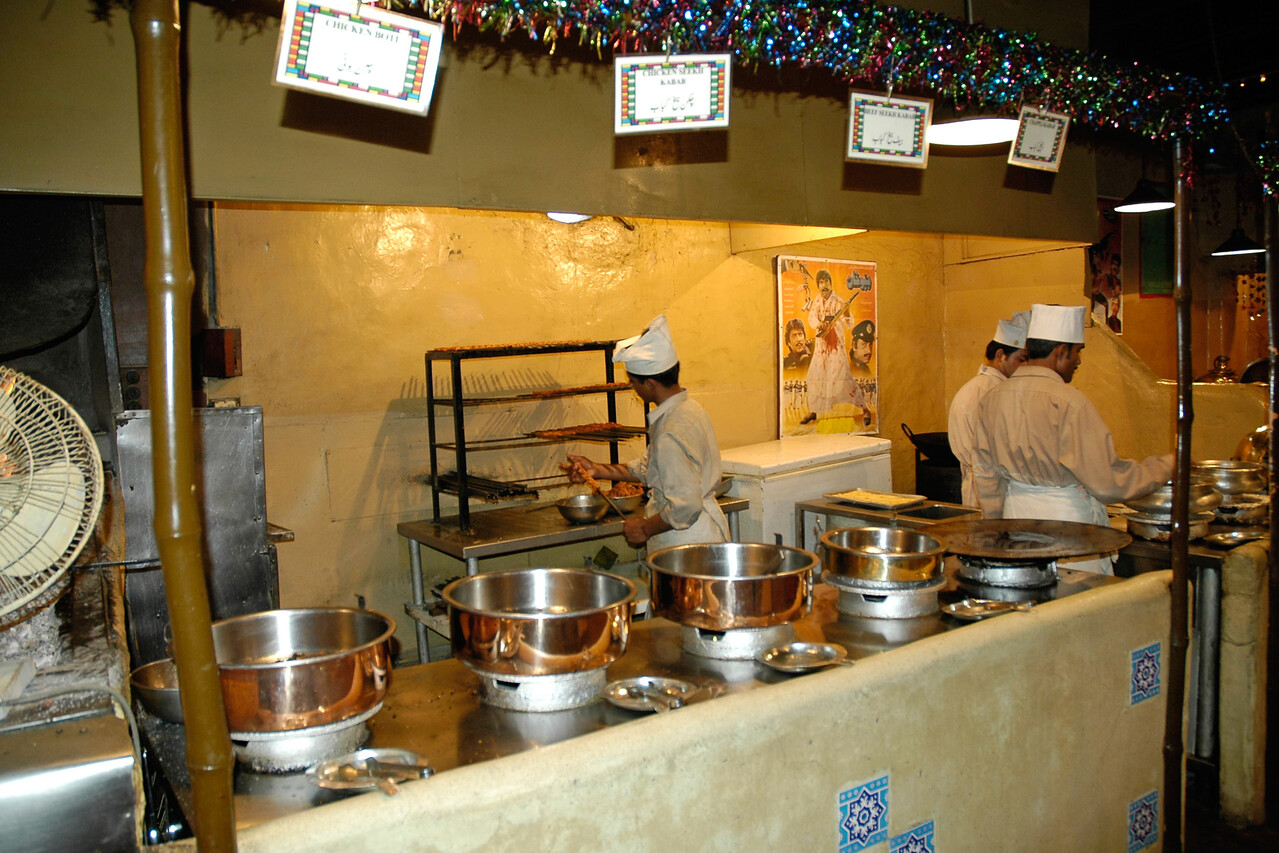 Lunch at a nice fancy restaurant in Lahore, Pakistan. Kebabs being prepared. You can you see some orange jalebis (sweets) in the foreground.