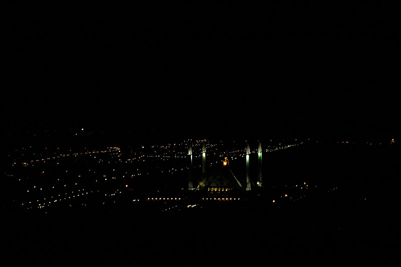 View from Marghallas Hills of Faisal Mosque, Islamabad. This is the largest mosque in Pakistan and South Asia and the fourth largest mosque in the world. Faisal Mosque is the National Mosque of Pakistan. It has a covered area of 5,000 sq mtr (54,000 sq ft) and has a capacity to accommodate approximately 300,000 worshippers (100,000 in its main prayer hall, courtyard and porticoes and another 200,000 in its adjoining grounds). <br /> <br /> The Faisal Mosque is named after the late King Faisal bin Abdul Aziz of Saudi Arabia, who supported and financed the project.<br /> <br /> Location: Islamabad, Pakistan.