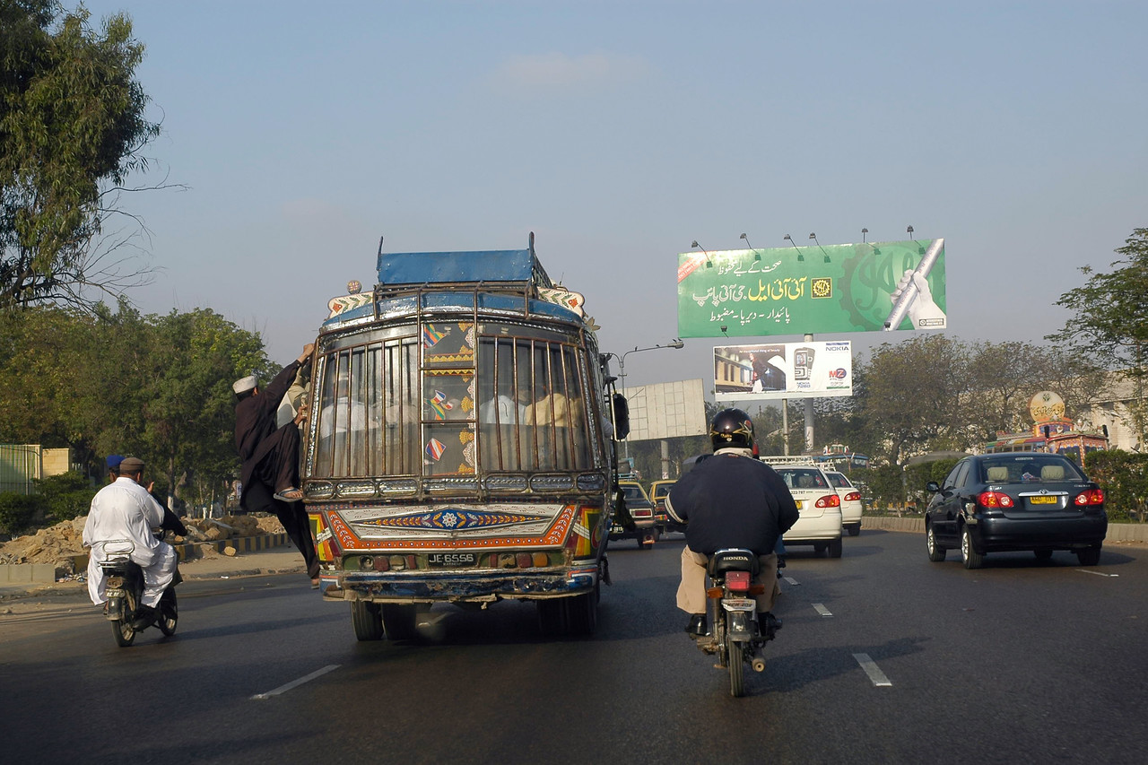 Overcrowded and over flowing buses on the streets of Karachi, Pakistan