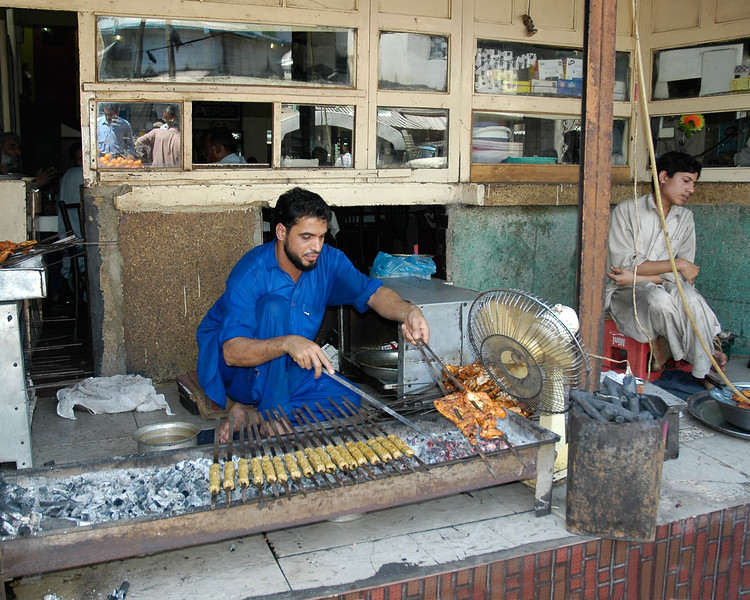 Grilled chicken, sheekh kebabs and other foods being cooked on open charcoal fire in Karachi, Pakistan.