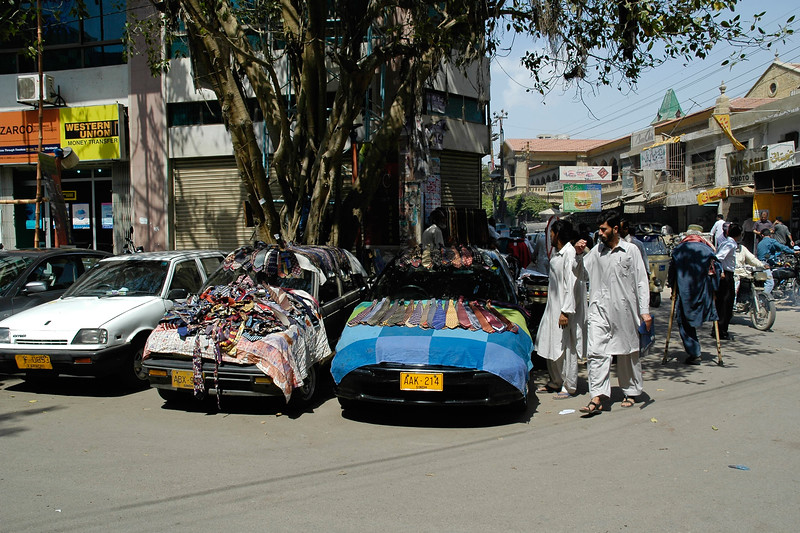 Innovative use of space. Selling items put on display on top of cars in the packed streets of Karachi, Pakistan