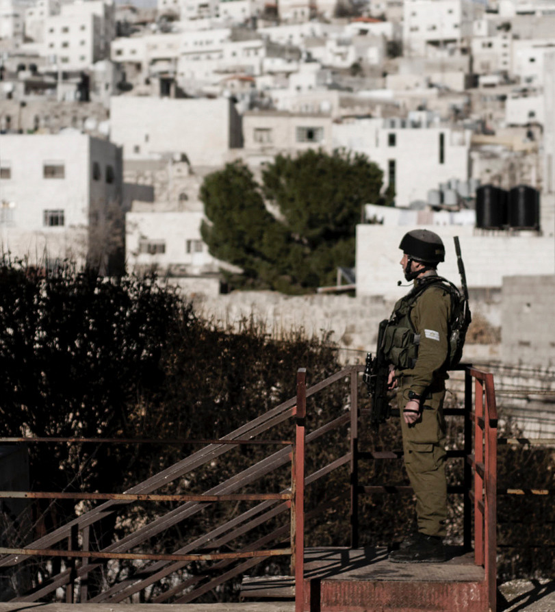 Since early 1997, following the Hebron Agreement, the city of Hebron has been divided into two sectors: H1 and H2. The H1 sector, home to around 120,000 Palestinians, came under the control of the Palestinian Authority. H2, which was inhabited by around 30,000 Palestinians, remained under Israeli military control to protect several hundred Jewish residents in the old Jewish quarter. A large drop has since taken place in the Palestinian population in H2, identified with the impact of extended curfews, strict restrictions on movement with 16 check-points in place, the closure of Palestinian commercial activities near settler areas, and settler harassment.<br /> <br /> Soldier on guard duties inside a Jewish settlement overlooking the old Palestinian city of Hebron. 2012.