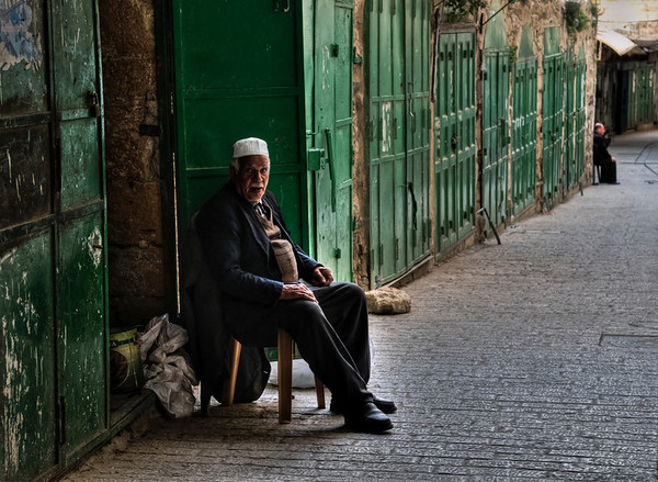 The old city of Hebron is characterized by narrow, winding streets, flat-roofed stone houses, and old bazaars.   Shop keeper, Hebron, Palestine, 2012.