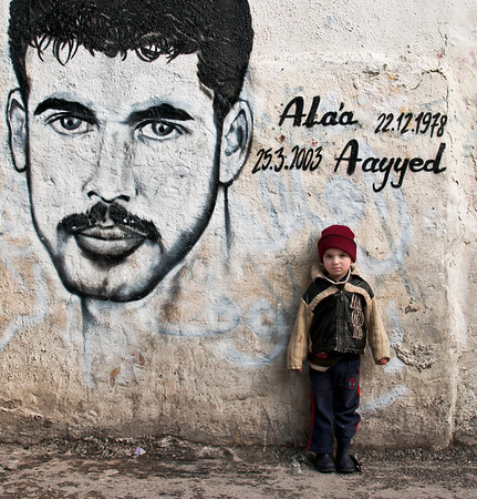 A small boy stands alone in front of a mural of his late father. A suicide bomber (martyr)  in the Aida refugee camp.   Bethlehem, Palestine, 2012.