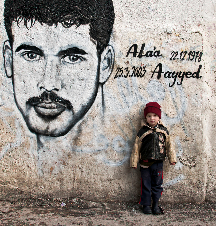 A small boy stands alone in front of a mural of his late father. A suicide bomber (martyr)  in the Aida refugee camp. <br /> <br /> Bethlehem, Palestine, 2012.