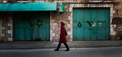The forced closure of muslim shops suffer the indignity of being sprayed with the star of david, whilst a muslim woman walks the deserted streets of what was once a busy palestinian thoroughfare, now inside an area controled by the IDF the Israelies like to call a buffer zone.  Hebron, Palestine, 2012.