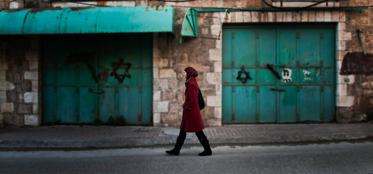 The forced closure of muslim shops suffer the indignity of being sprayed with the star of david, whilst a muslim woman walks the deserted streets of what was once a busy palestinian thoroughfare, now inside an area controled by the IDF the Israelies like to call a buffer zone.<br /> <br /> Hebron, Palestine, 2012.