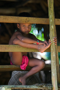Embera boy sitting on the rail, Chagres National Park, Panama.