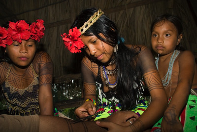 Embera girls painting dye on tourist, Chagres National Park, Panama.