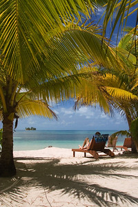 Relaxing in lounge chair on the beach of South Water Caye, Stann Creek, Belize.