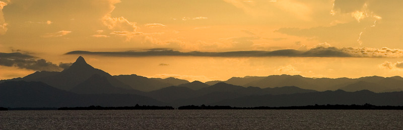 View of Victoria Peak at sunset from south beach of South Water Caye, Stann Creek, Belize.