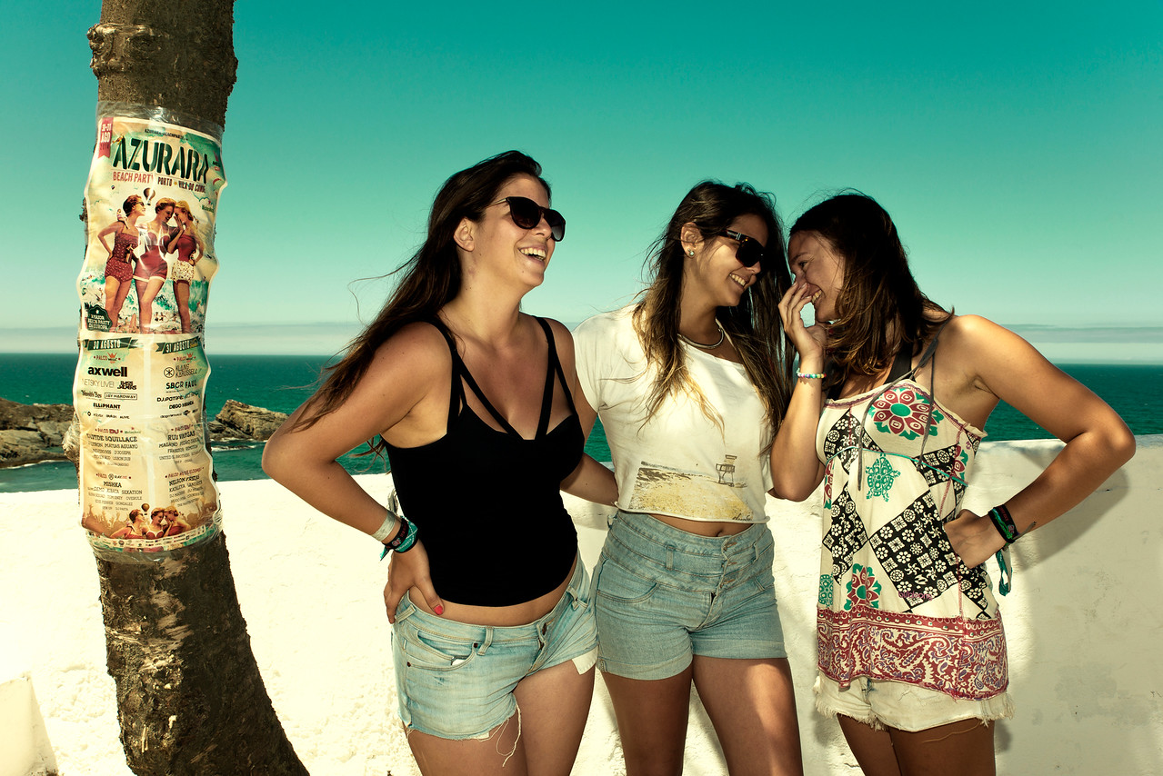 Three young women having fun mimicking a poster advertising a music festival.<br /> <br /> Costa Vicentina, Portugal, 2014.