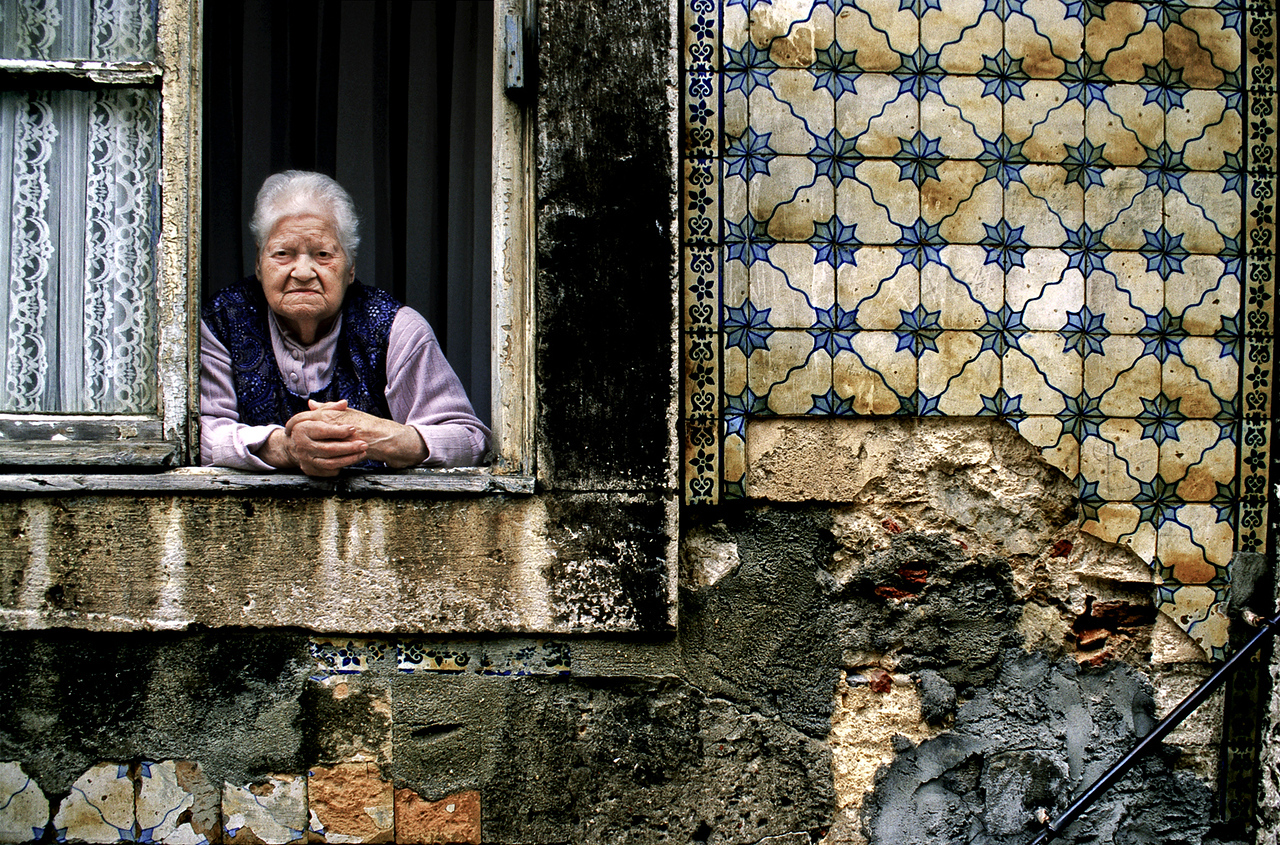 Woman looking out of her worn out apartment in the Alfama district.  Dilapidated and sometimes dangerous, this area is the home of the traditional Fado music. Walking through its narrow lanes one comes to understand the melancholy expressed in most of the Fado tunes.<br /> <br /> Lisboa, Portugal.