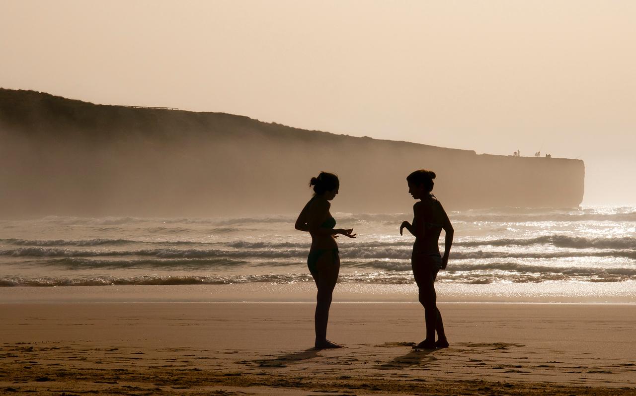 Women chatting on a beach near the village of Aljezur, Costa Vicentina, Portugal.