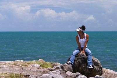Beautiful woman on rocks at edge of the Caribbean Sea in Punta Gorda Town, Toledo.