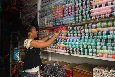 Woman shopping in store looking at cloth and threads. Punta Gorda Town, Toledo, Belize.