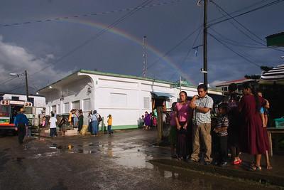 People waiting on fruit vendors on corner street at Punta Gorda market, Toledo, Belize.