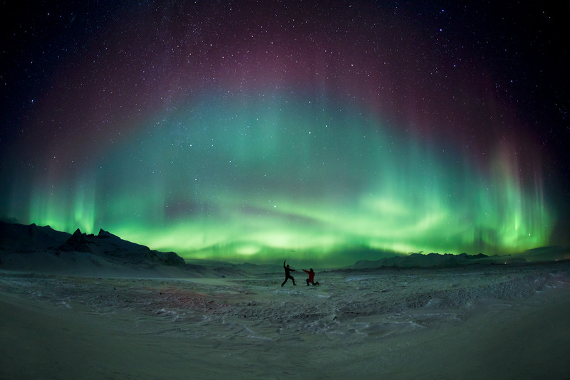 People fighting under Aurora Borealis