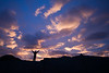 Silhouette of person with raised arms against dramatic sunset sky, Norway, Scandinavia