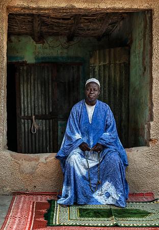 Local man in traditional dress holding prayer beads.  Diembéreng, Senegal, 2020
