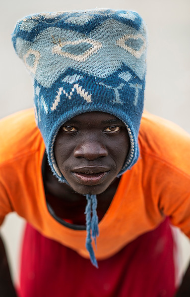 Portrait of a fisherman wearing a padded hat used to carry heavy boxes laden with fish.  Casamance, Senegal, 2020.