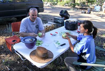 Doug (FishPOET) and Jim (Teotwaki)'s daughter peal apples for Dutch Oven Apple Cobbler.  Yum!