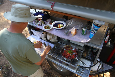 Dave (CynRat) prep's their dinner contribution at his well set up Adventure Trailer