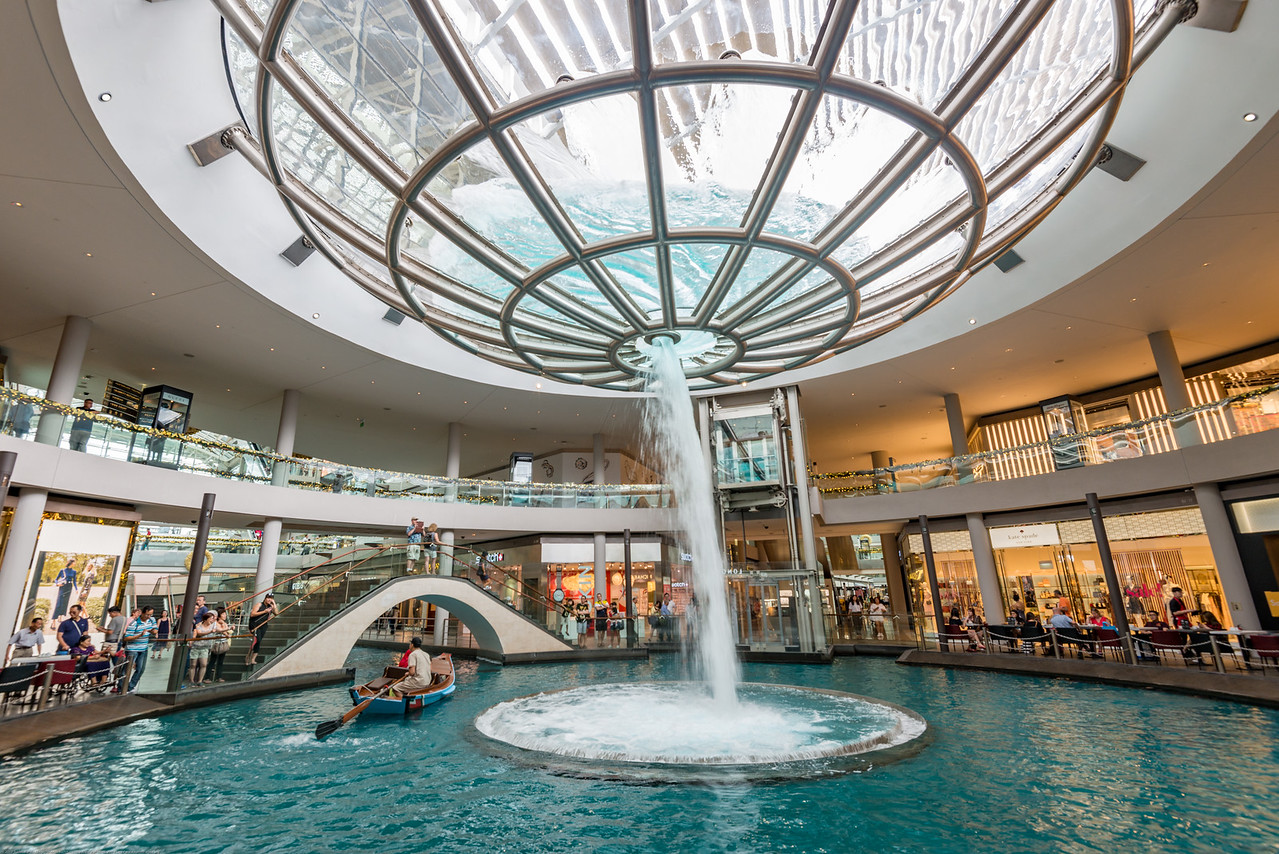 Whirlpool, Marina Bay Sands. A large whirlpool forms inside a 70- foot diameter acrylic bowl and falls 2 stories to a pool below.  A canal runs through the length of the shoppes, in the same style as the Venetian in Las Vegas. Sampan rides on the canal are available for guests and shoppers at the shopping mall, similar to the gondola rides available in the Venetian.<br /> <br /> The Whirlpool, a collaboration with architect Moshe Safdie, functions as both a skylight and a rain collector. The rain water is recycled back to the whirlpool and also fills a canal that runs through. Marina Bay located in Central Area, Singapore. A large whirlpool forms inside a 70- foot diameter acrylic bowl and falls 2 stories to a pool below. The artwork, a collaboration with architect Moshe Safdie, functions as both a skylight and a rain collector. The rain water is recycled back to the whirlpool and also fills a canal that runs through the atrium. Marina Bay located in Central Area, Singapore