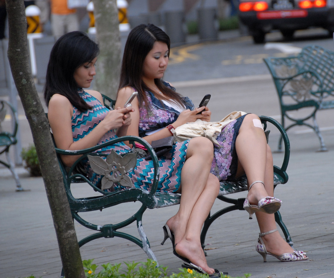 """Texting (Sending SMS messages). Street scenes. <br /> The Fountain of Wealth (Chinese: 财富之泉), Singapore.<br /> <br /> The Guinness Book of Records in 1998 listed this as the largest fountain in the world. Located in one of Singapore's largest shopping malls, Suntec City, at regular intervals, the fountain is turned off and visitors are invited to walk around a mini fountain at the centre of the fountain's base for good luck. At night, the fountain is the setting for laser performances, as well as """"live"""" song and laser message dedications."""