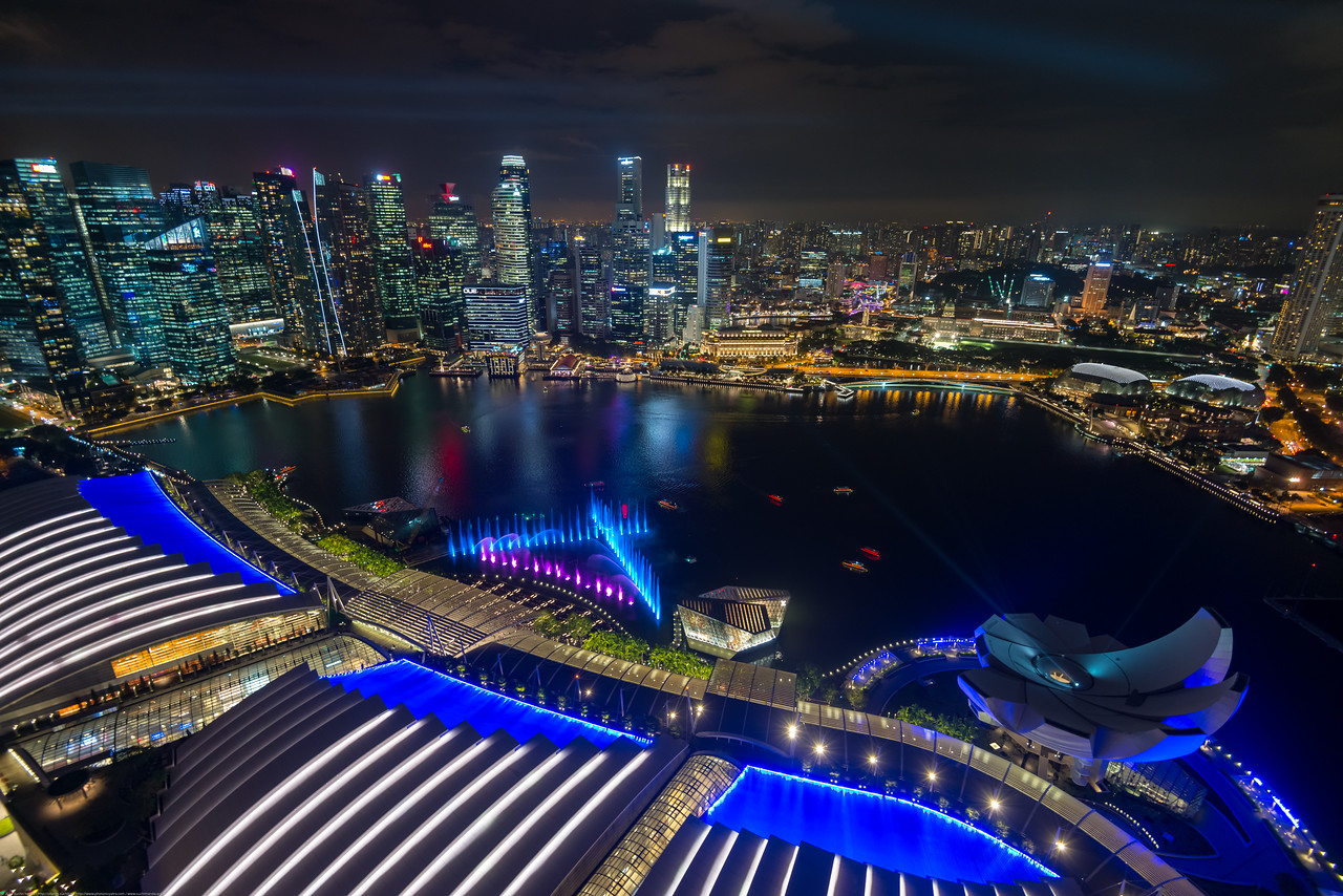 "Ariel view of ""Spectra - A Light And Water Show"" and CBD Singapore, seen from Sands SkyPark Observation Deck on the 57th floor. The deck has panoramic city views & 2 upscale restaurants and a pool for hotel residents."