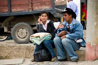 A couple caring for their baby in the street.