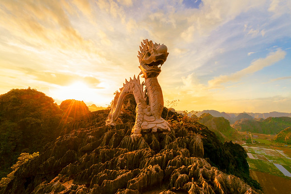Taken atop Mua Cave in Ninh Binh, Vietnam.  This photo has everything I was hoping for and beyond.  The rice paddies are flooded in the lower right.  The karst mountains surround the peak.  This dragon statue stands about 12 feet tall.  And if you look closely, in between the dragons tail there is a sleeping mans face