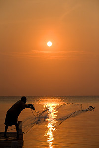 Fisherman casts net off the pier at South Water Caye.