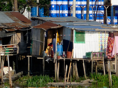 Houses resting on poles next to the Guayas river
