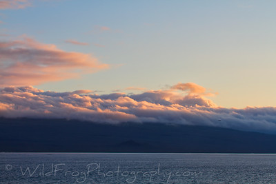 Clouds rolling over the hills on San Cristobal Island at Sunset