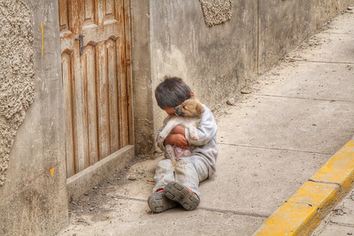 Local kid playing with his puppy in the street, Ollantaytambo, Peru