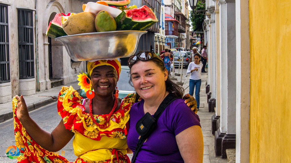 Reverse culture shock symptoms include wanderlust. This photo of Linda and a fruit vendor was taken in Cartagena, Colombia.