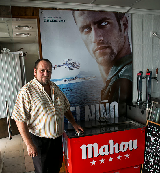 A proud father poses in front of a signed poster featuring his son, the main actor in a movie.  The father owns a chureria (fritters) shop were his two other sons also help from time to time.