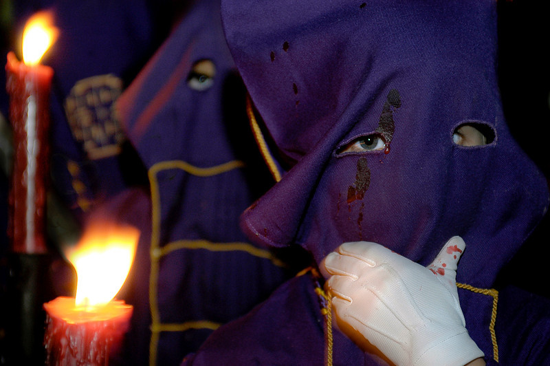 Holy week in Easter is a time of great devotion in Spain. In this picture you can see members of a religious fraternity known as 'Nazarenos' making their way along the narrow streets of Arcos de la Frontera. They cover their faces with a traditional mask and carry candles to light the way. Some are barefoot in an act of penance. <br /> <br /> Arcos de la Frontera, Andalucia, Spain.