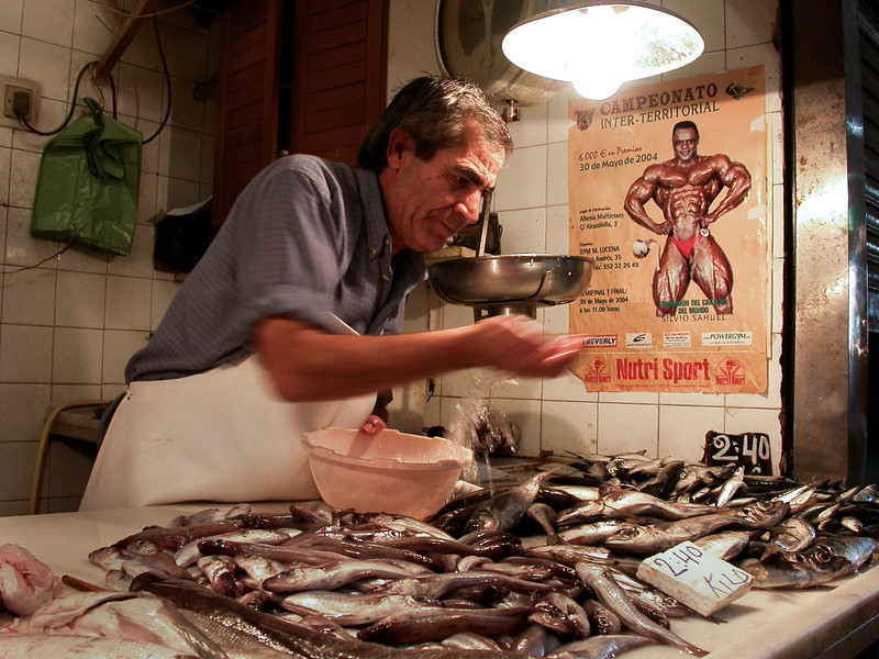 Fishmonger at a fish market.<br /> <br /> Malaga, Andalucia, Spain.